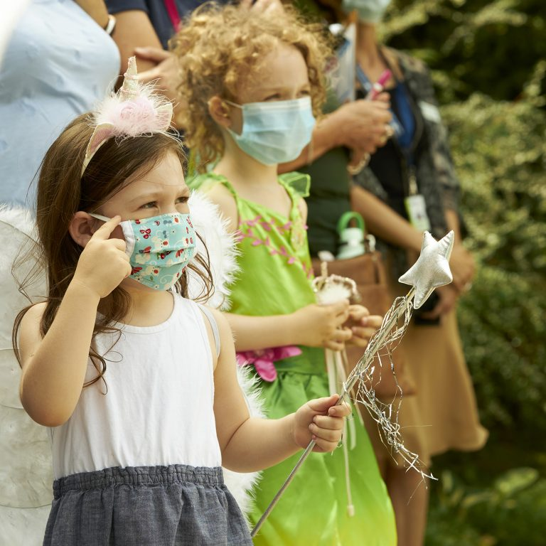 Two young girls wearing fairy wings and holding wands. They are both wearing face masks.
