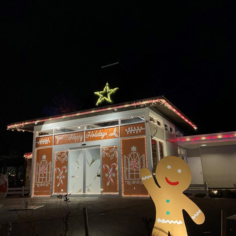 cutout gingerbread person waving in front of the teahouse decorated like a gingerbread house