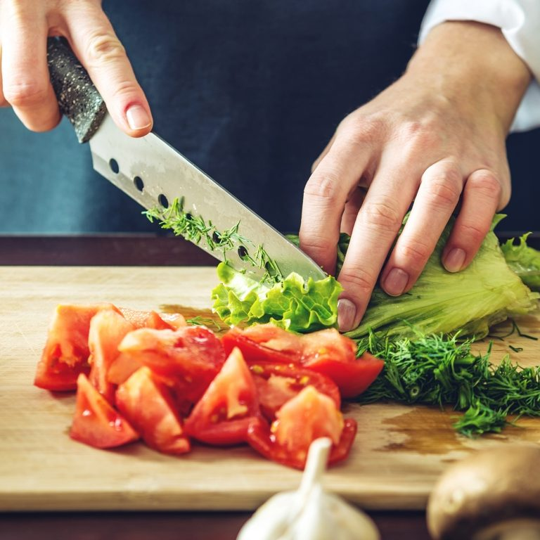 Chef Chopping tomatoes, lettuce and herbs on a cutting board