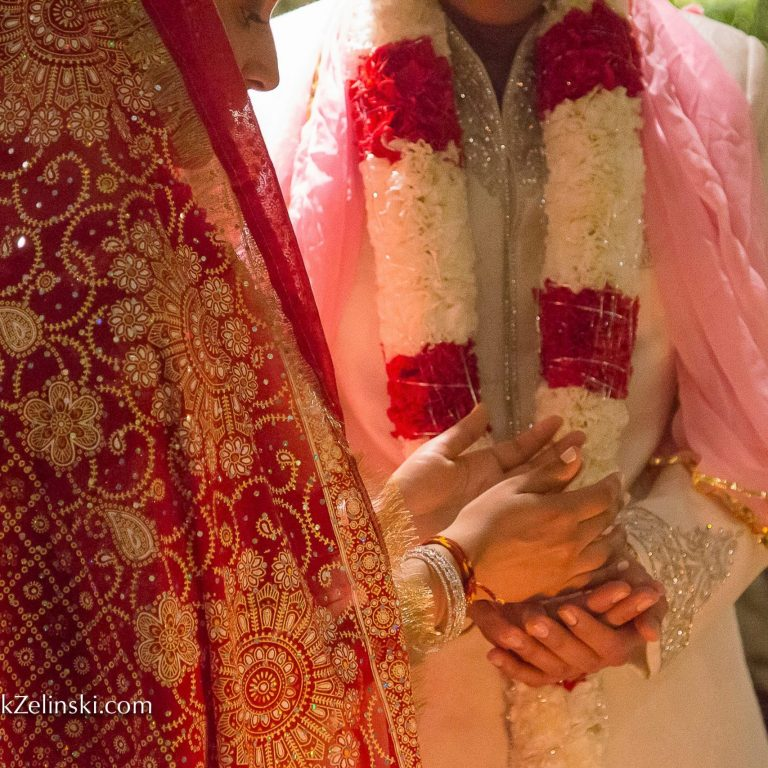 Bride and groom standing close and putting their hands together in Hindu ceremony
