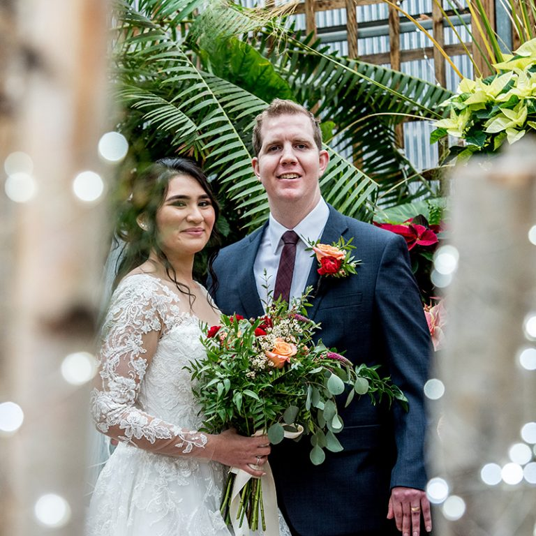 Bride and Groom in breezeway decorated for the holidays