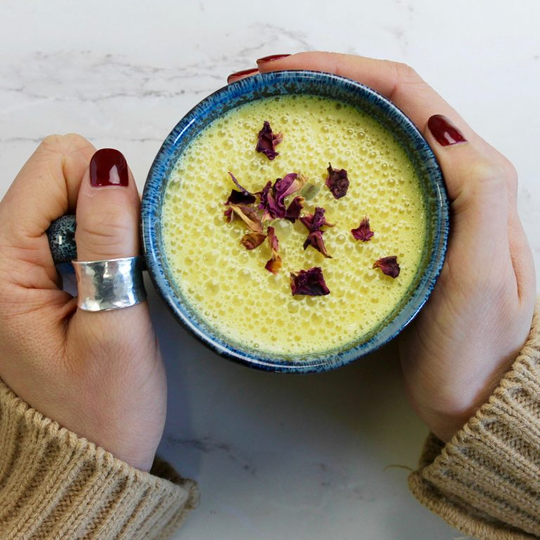 Hands holding cup of yellow turmeric tea