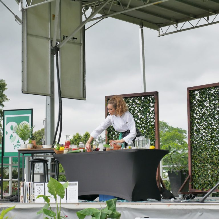 Chef Amy Symington giving a cooking demonstration on the Blooms Stage