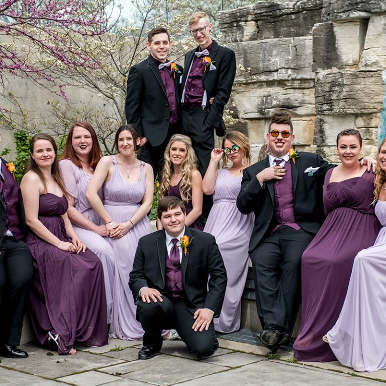 Wedding party sitting in courtyard with redbuds blooming