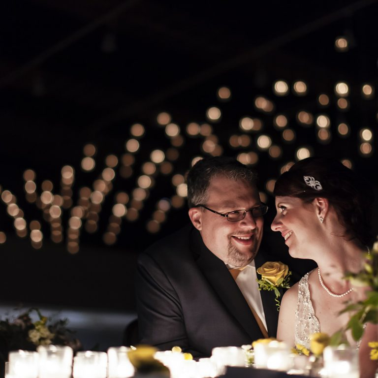 Bride and Groom sitting at table in dark reception hall with romantic lighting