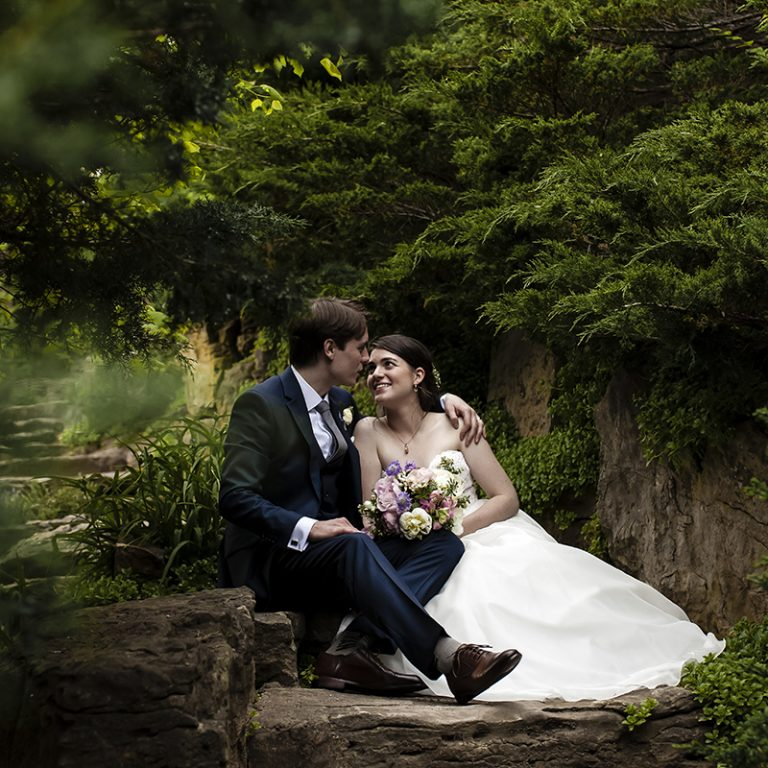Bride and Groom sitting on stone staircase surrounded by evergreen