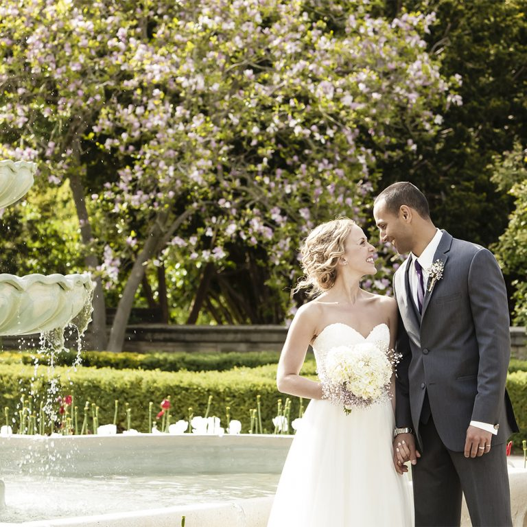 Bride and groom in scented garden beside fountain