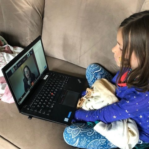 Child watching educational video on laptop