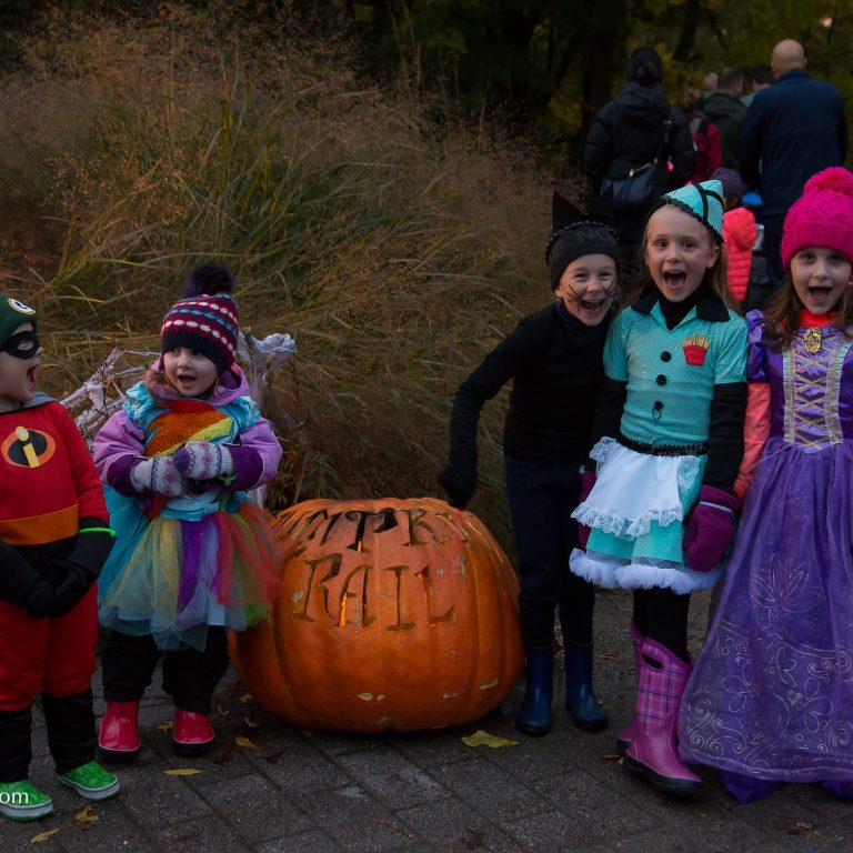 Children in costume standing around large carved pumpkin