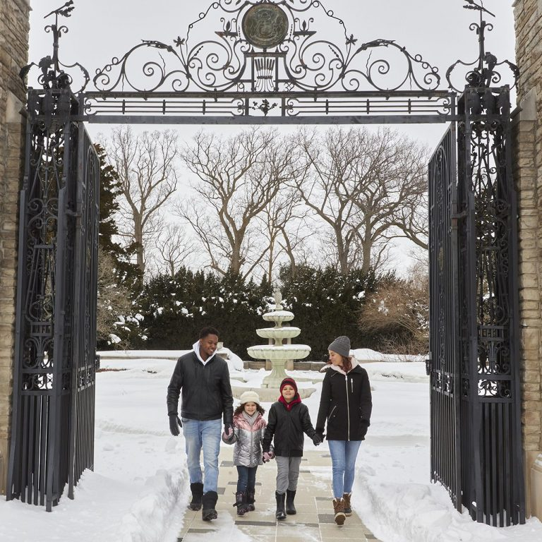 Family of four walking through Hendrie Park Gates in winter