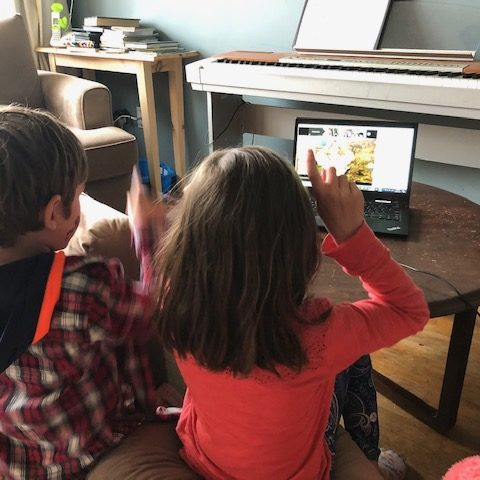 two kids watching a video on a laptop