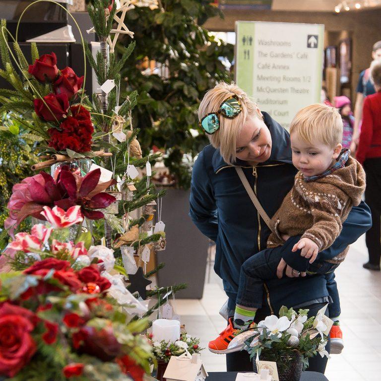 woman and toddler looking at holiday displays at shop