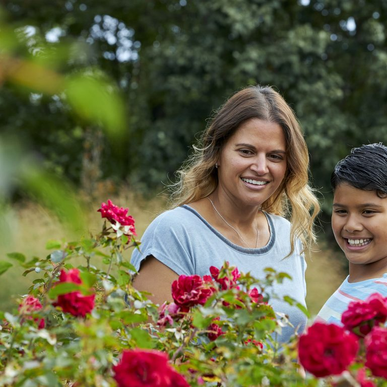 mother and daughter looking at red roses