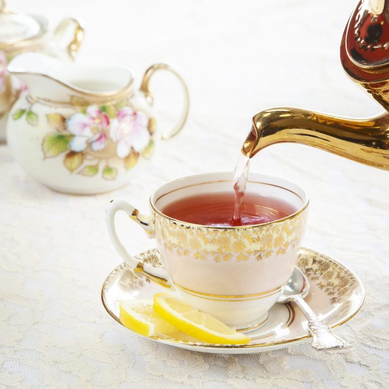 pouring tea into fine china cup with formal high tea setup